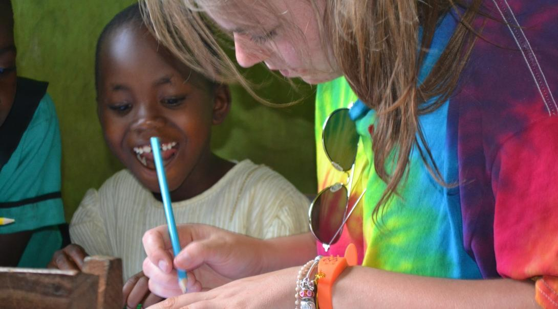 A child listens to a Childcare volunteer explain an English writing activity at a school in Ghana.